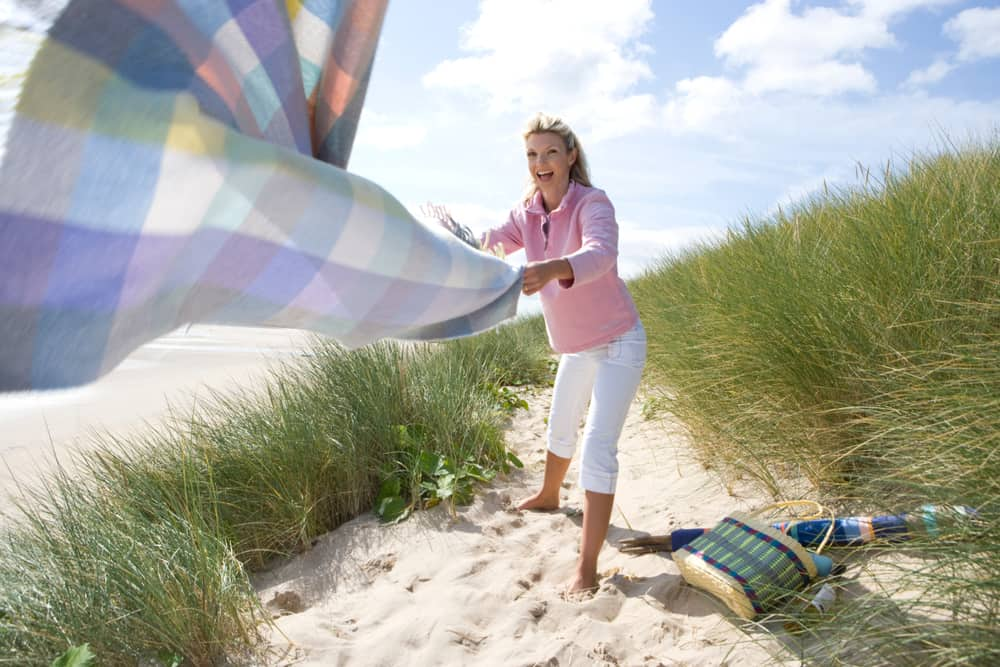 Woman putting a pastel checkered blanket on sand dunes by beach.