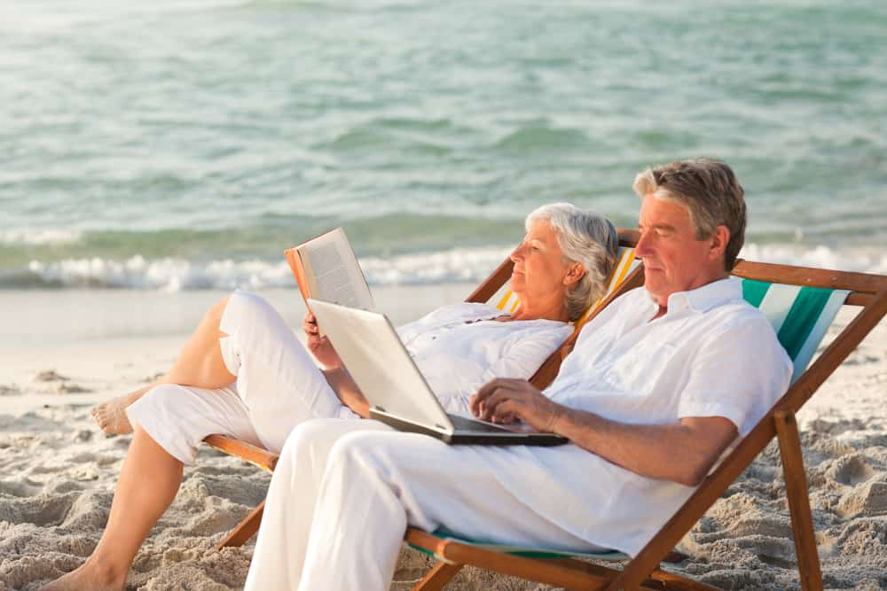 Elder couple sitting on a lounge chair while reading and working on a laptop.