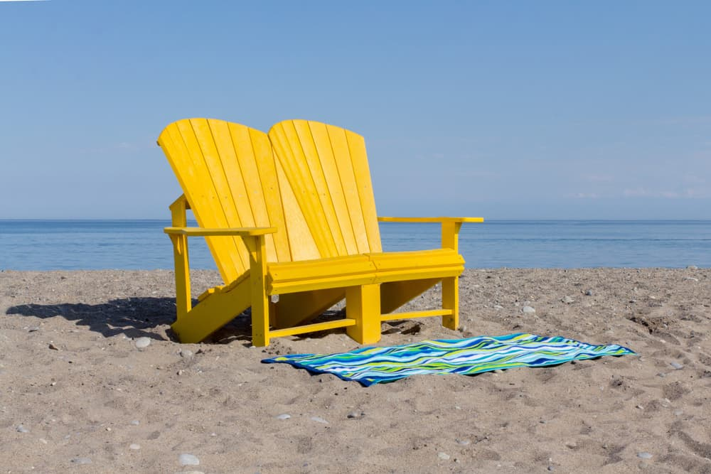Yellow loveseat beach chair and a striped beach towel on the sand.