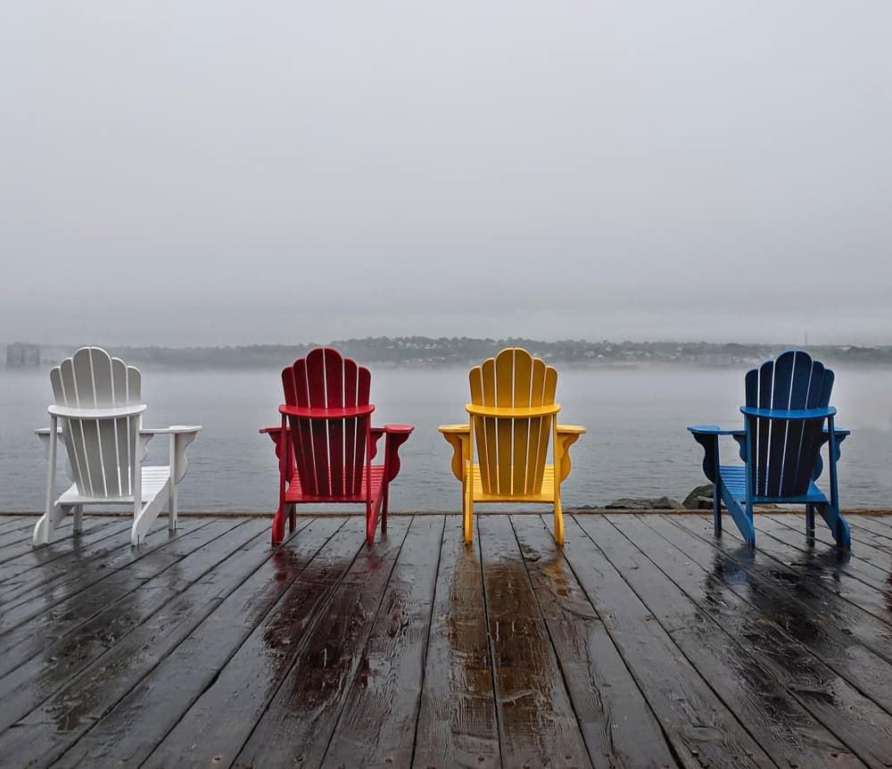 A row of multicolored beach chairs on a deck facing the sea.