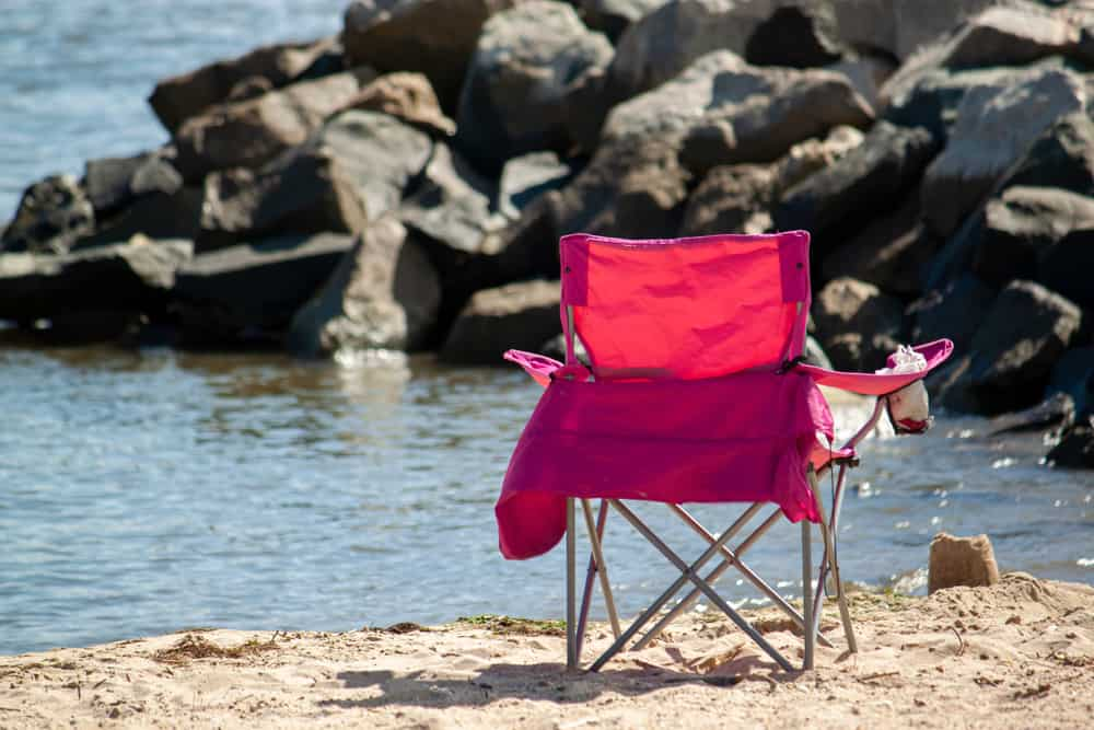 Red beach chair with cupholder by the seashore.