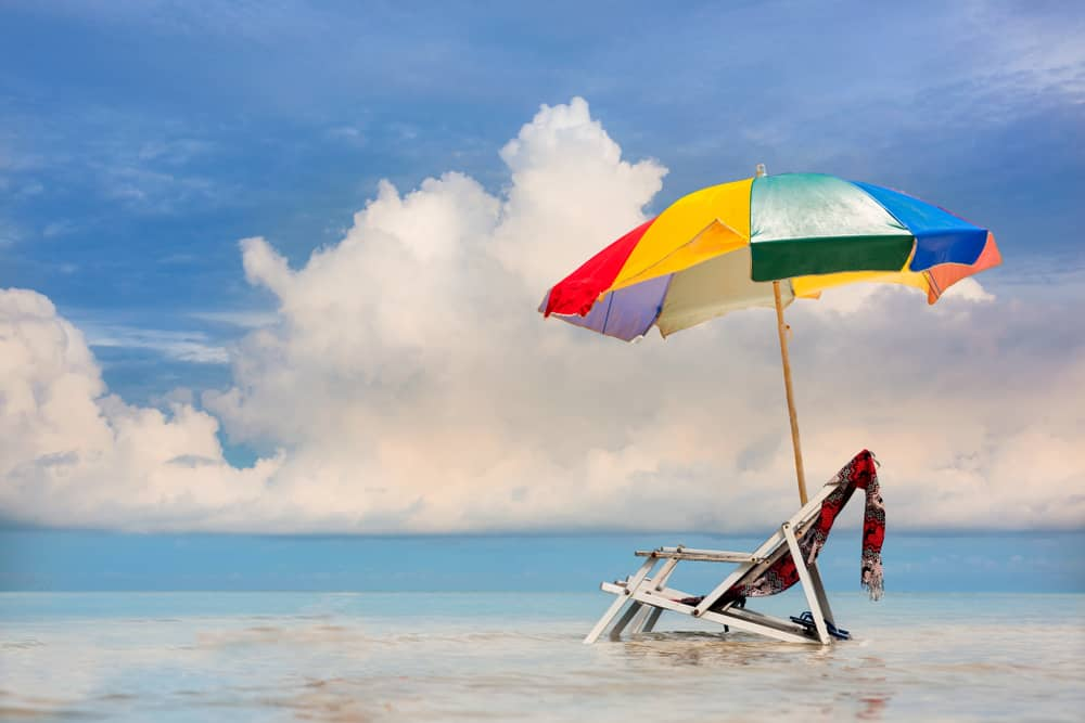 Beach chair with umbrella in the sea.