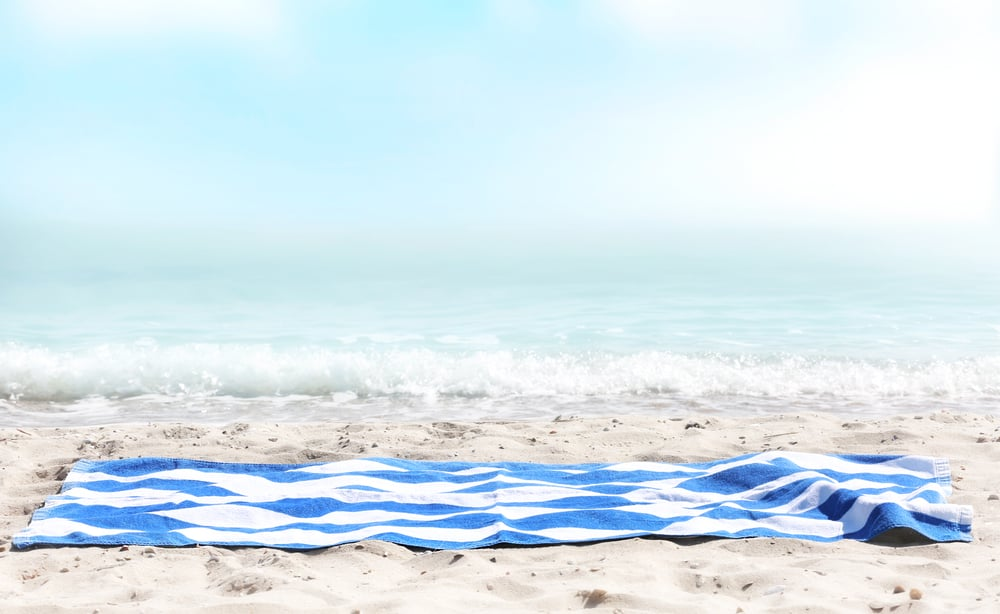 Blue stripped towel on sand,