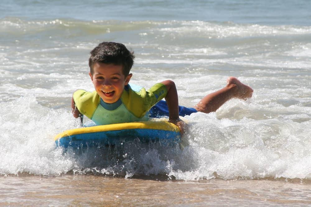 A boy surfing using a boogie board.