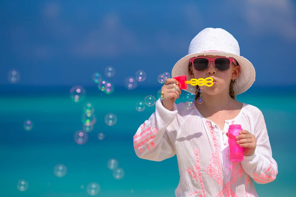 A girl making soap bubbles on the beach.