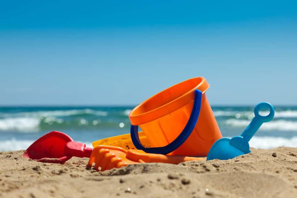 Orange bucket and shovels on the sand.