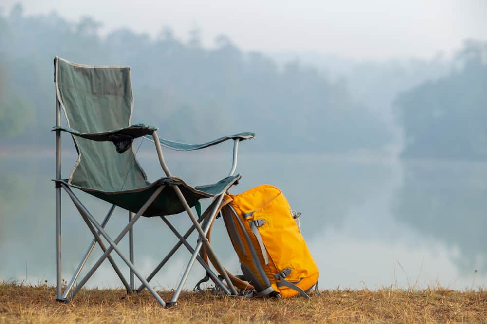Camp beach chair with yellow backpack on its side.