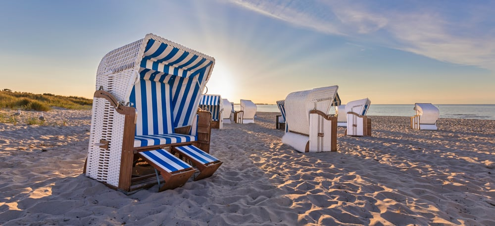 Canopy beach chairs on the sand.