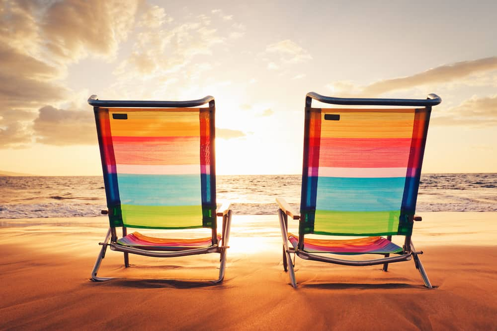 Two colorful beach chairs at sunset.