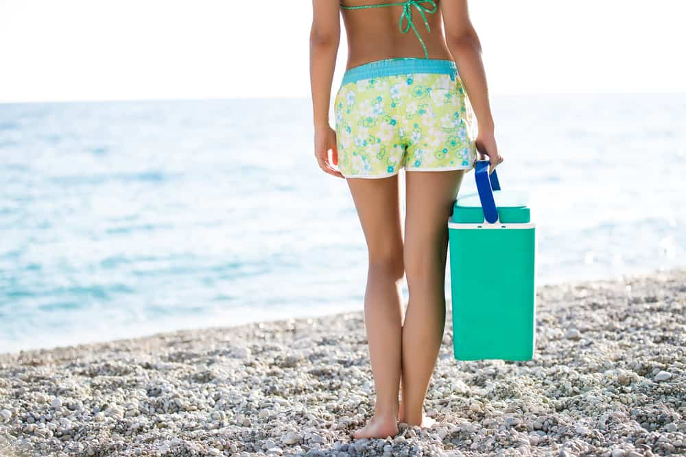 Woman carrying a cooler box by the seashore.