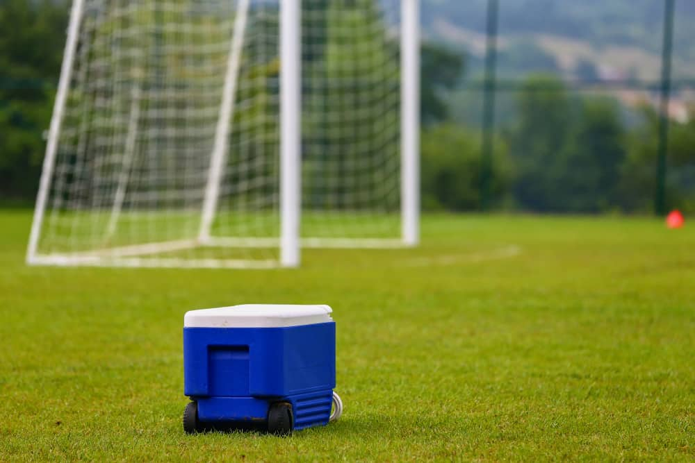 Wheeled cooler in the middle of football field.