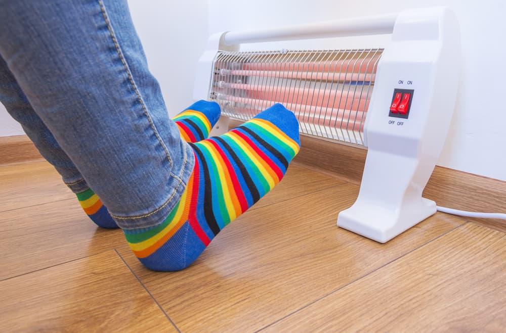 Woman in rainbow socks warms her feet on the fan heater.