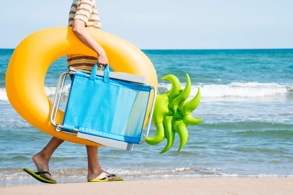 A man carrying a folding beach chair and swim ring by the seashore.