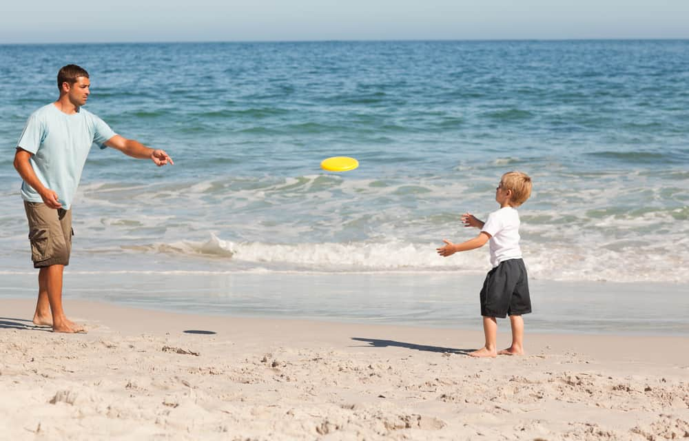 A boy playing frisbee with his father.