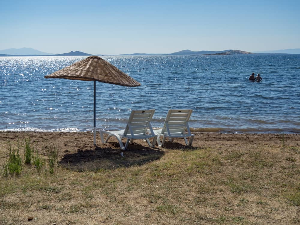 A couple of heavy duty beach chairs and umbrella by the seashore.