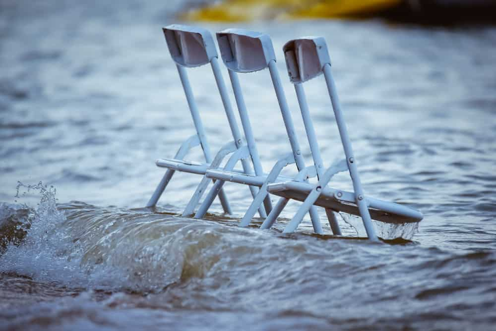 Silver high back chairs in the sea.