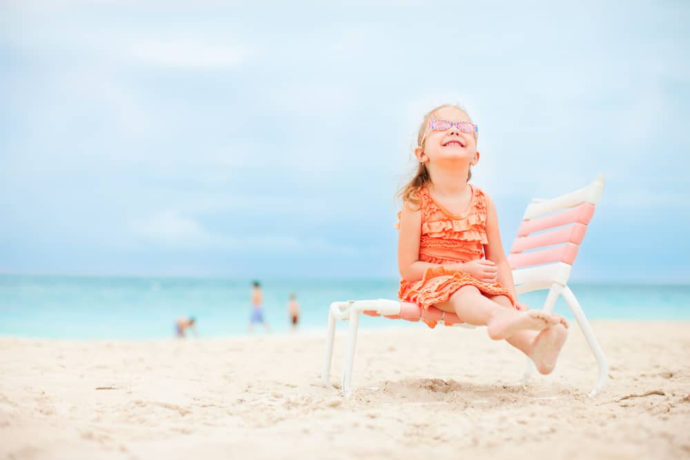 A girl sitting on a lounge chair at the beach.