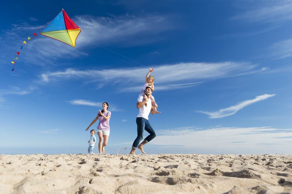 Family on the beach flying a kite.