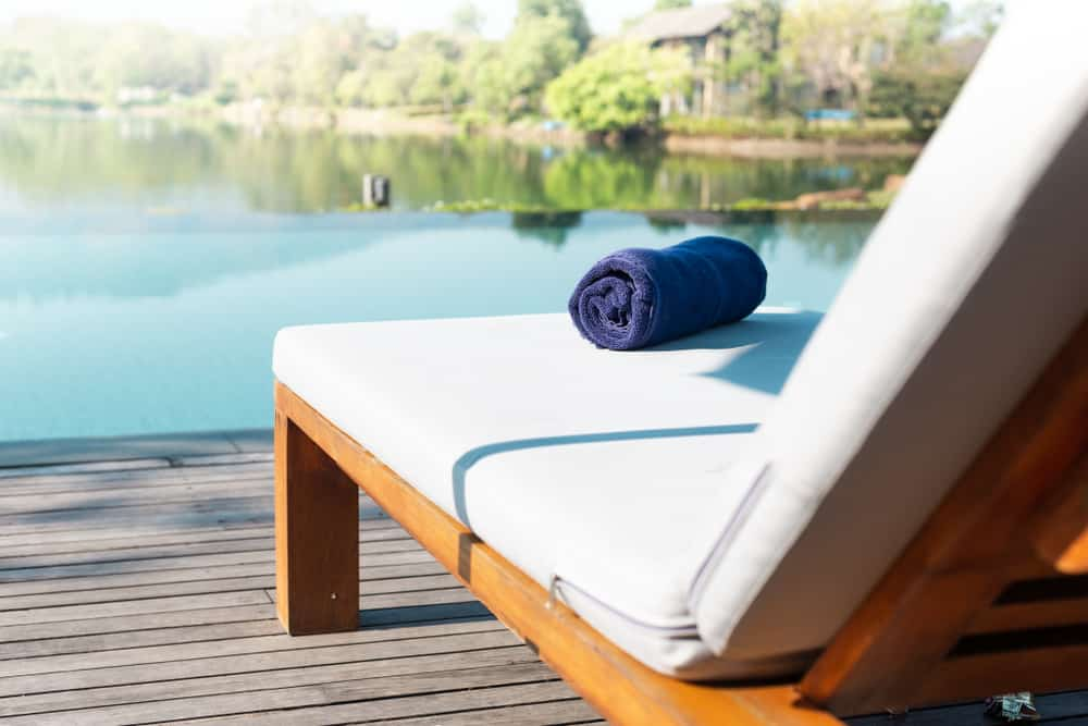 A closer look at a padded lounge chair with blue towel.