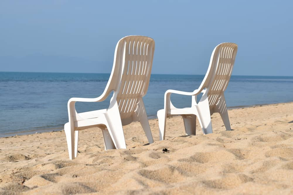 Two white plastic deck chairs on the sand facing the beach.