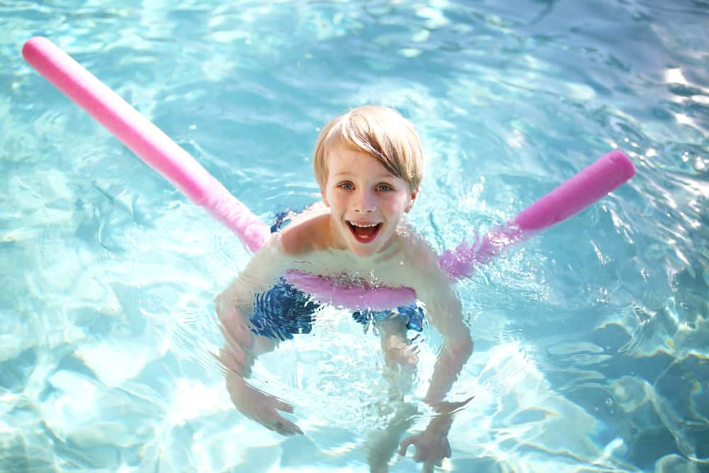 A boy swimming with a floating fun noodle in the pool.