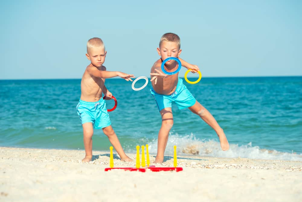 Little boys playing ring toss by the seashore.