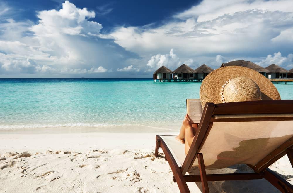 Woman on a sand beach chair reading a book,