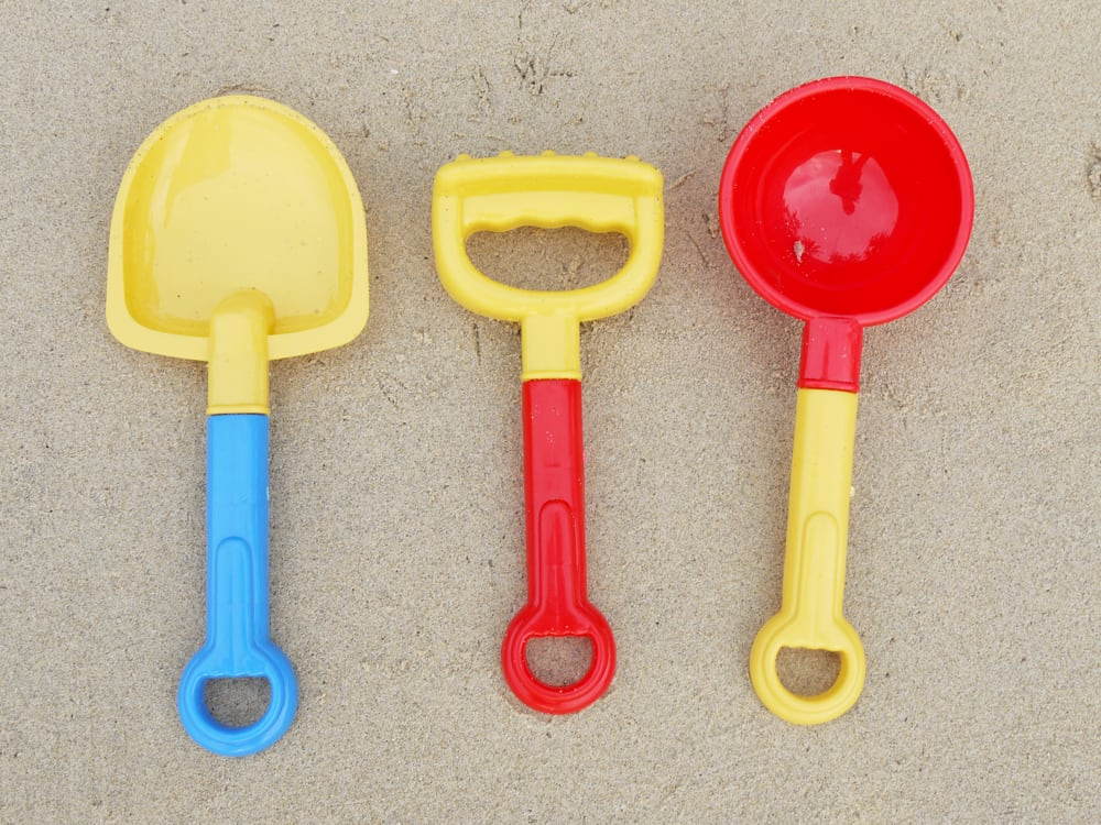 Colorful shovels on the sand.