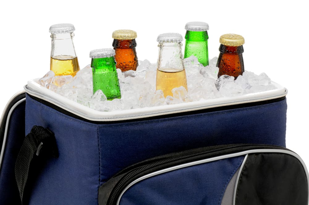 Soft-sided cooler filled with beer bottles and ice.