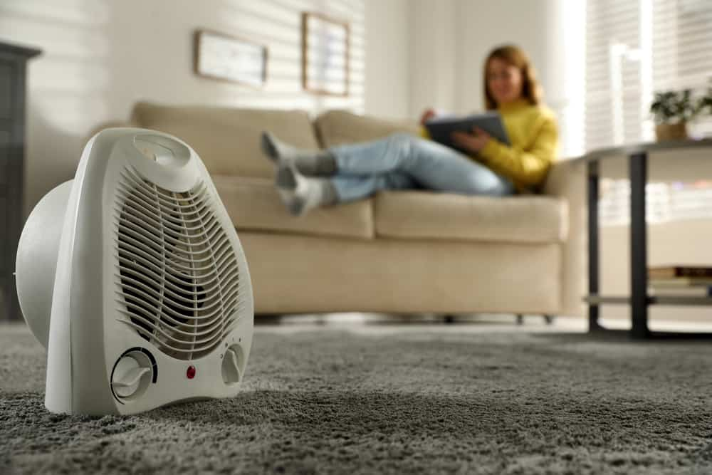 Space heater with a blurred lady on the background reading on a couch.