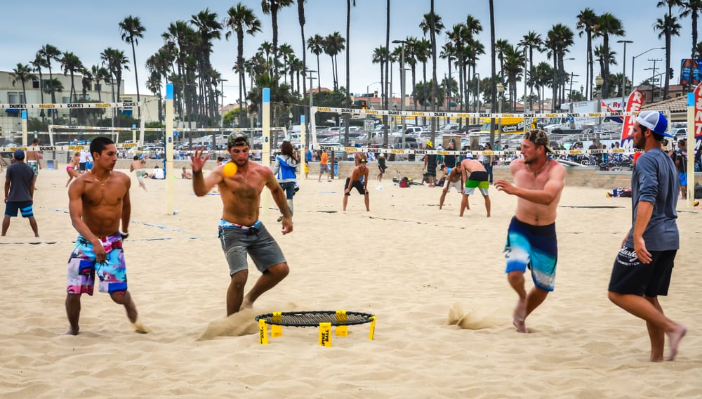 Group of men playing spikeball on the sand.