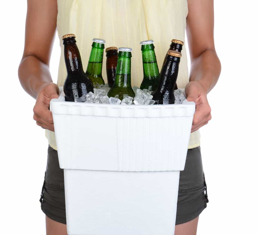 Woman carrying a styrofoam ice chest with bottles.