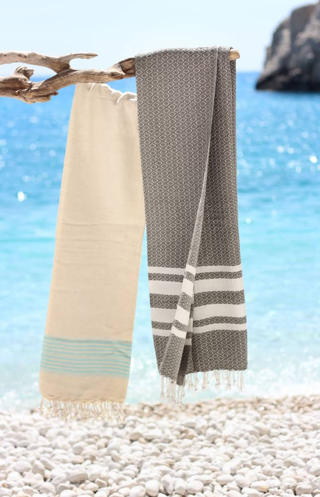 A couple of Turkish towels hanging on a branch near the beach.