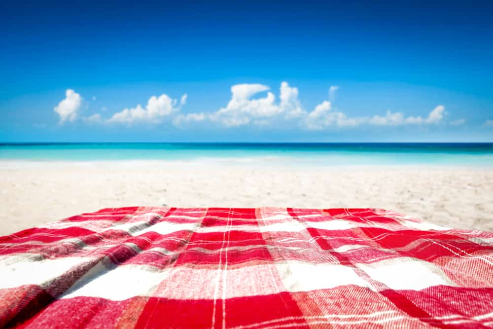 Red checkered blanket on sand.