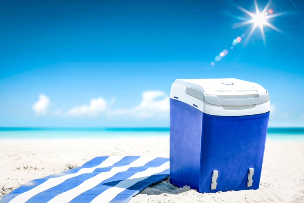 Blue cooler and a striped beach towel on the sand.