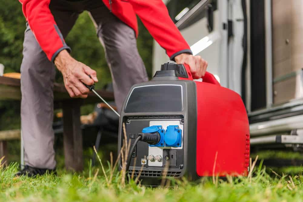 This is a close look at a man firing up the gas-powered portable generator.