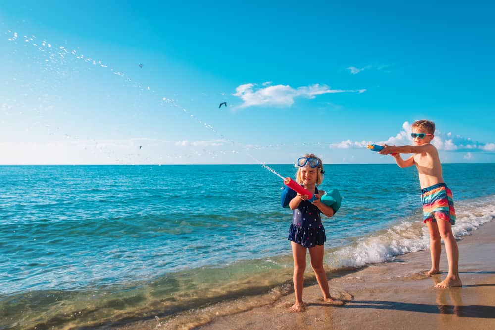 A girl and boy playing with water gun on the beach.