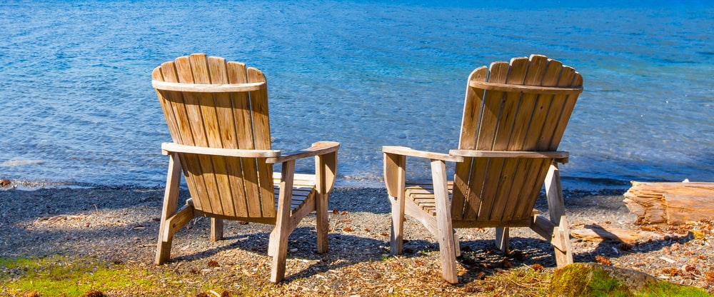 Two wooden chairs on the shore facing the lake.