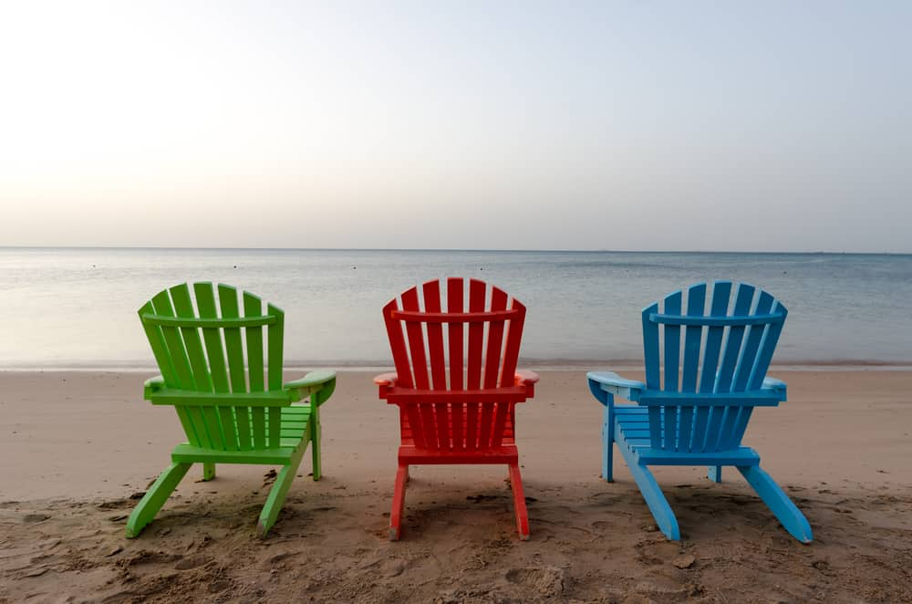 Multicolored wood chairs facing the beach.