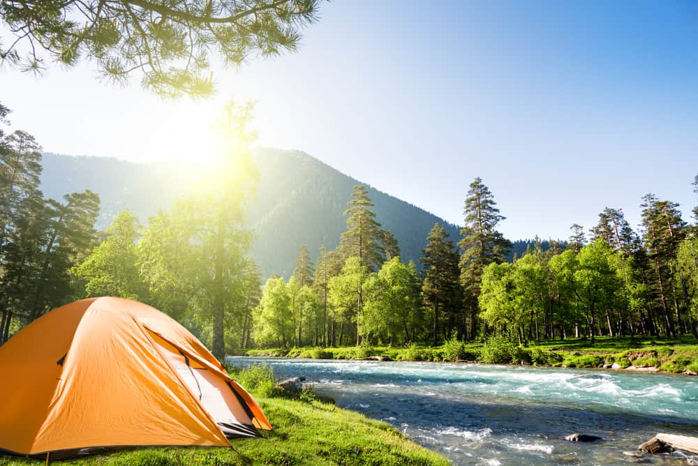 This is a pitched tent by the river at a free camping ground.