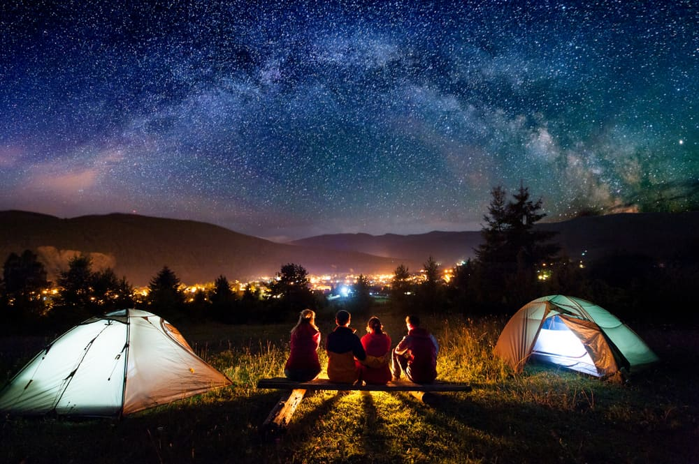 A group of friends camping on public lands with a couple of tents and campfire.
