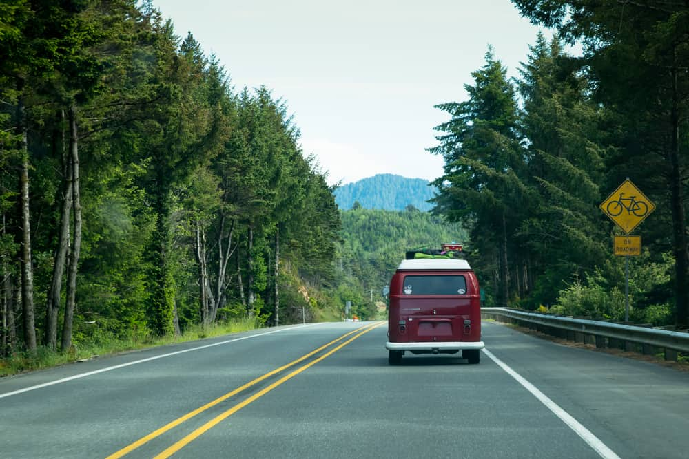 A red VW van driving along scenic Oregon Coast.