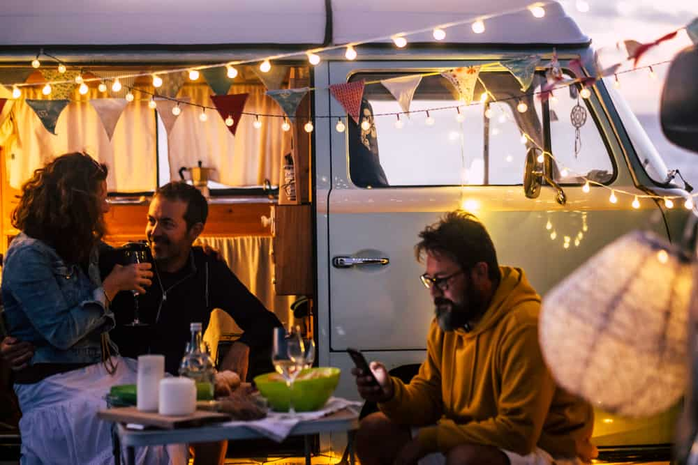 People having dinner outside a vintage van.