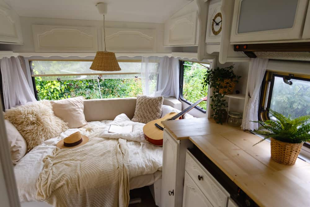Interior of a camper van with wooden cabinets, desk, and bed filled with fluffy pillows.