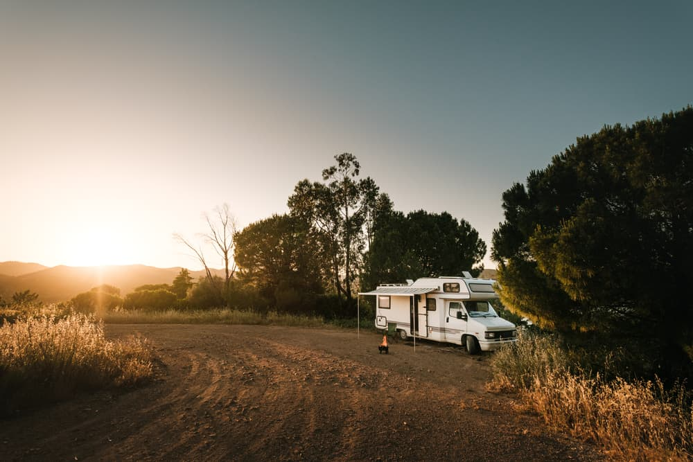 A white camper parked by the tall trees on the side of the dirt road.