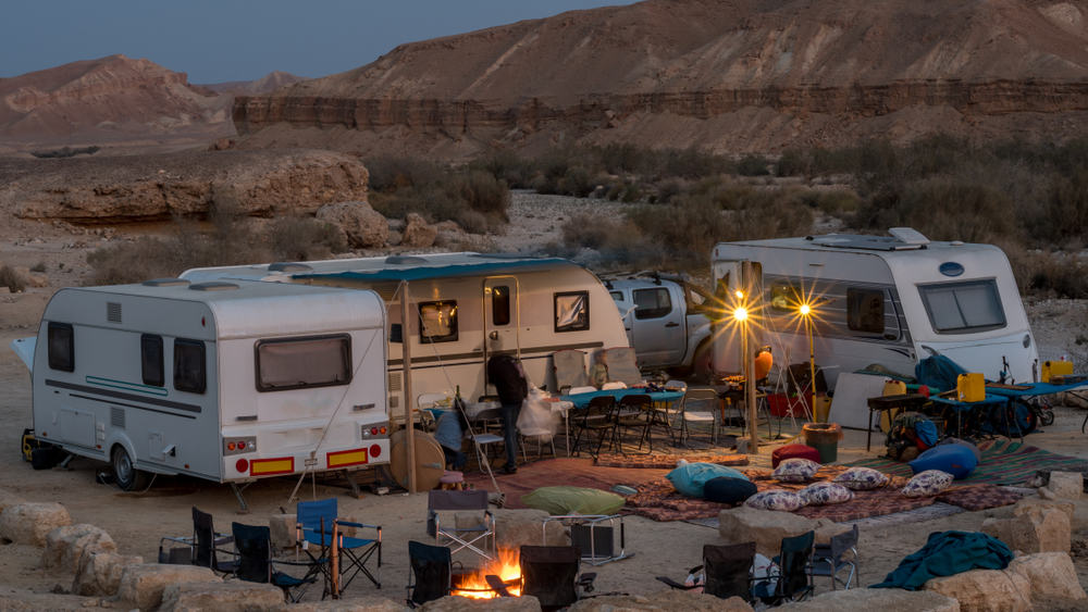 Multiple campers dry camping at a desert surrounded by rocks.
