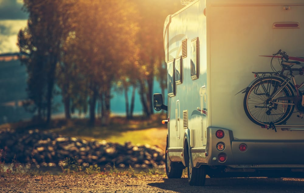 This is a close look at an RV camper parked by the lakeside trees.