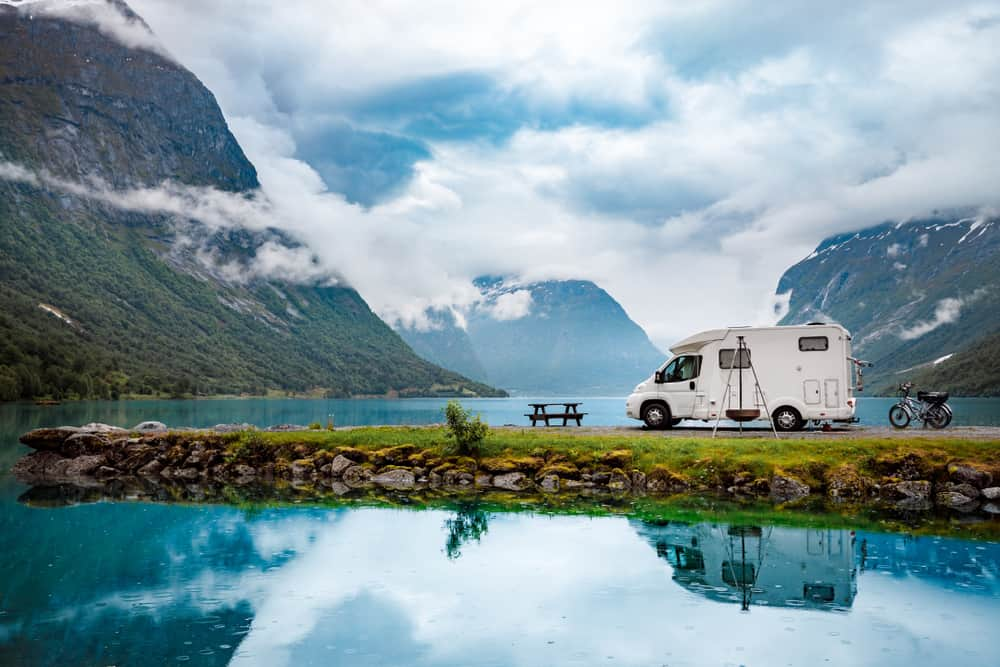 A white camper parked on the side of a large lake surrounded by tall mountains.