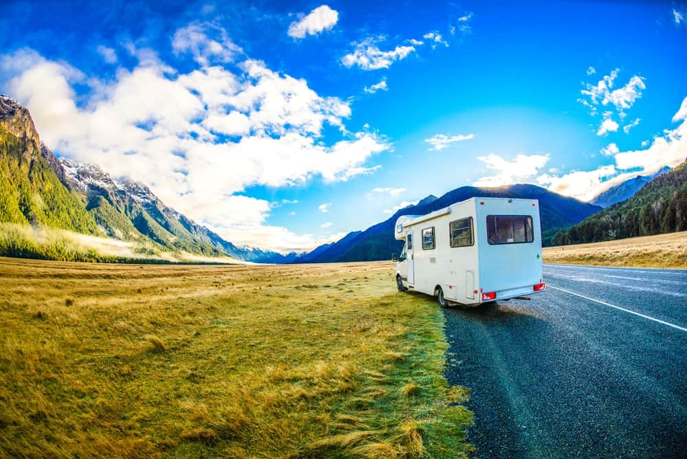 A camper about to park on the side of the road that has grass fields and mountain views.