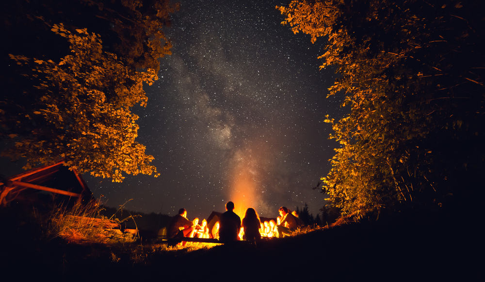 This is a nighttime view of a group of friends surrounding the bright campfire.